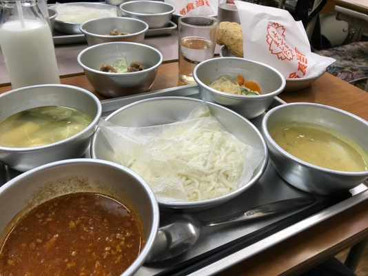 A full sampler. Small bowls clockwise from bottom left: Meat Sauce for Softmen (Large Bowl in center), Miso Soup, Deep-Fried Whale, Vegetable w/ Glass Noodles, Curry Stew. Milk is provided as well as Agepan (Fried Bread) in the rear right side of the picture.